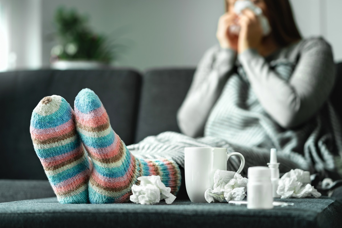 A woman in cozy clothes and surrounded by used tissues lounges on a couch.