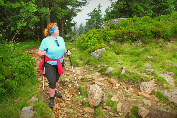 An overweight woman in a blue shirt hikes a rocky trail.