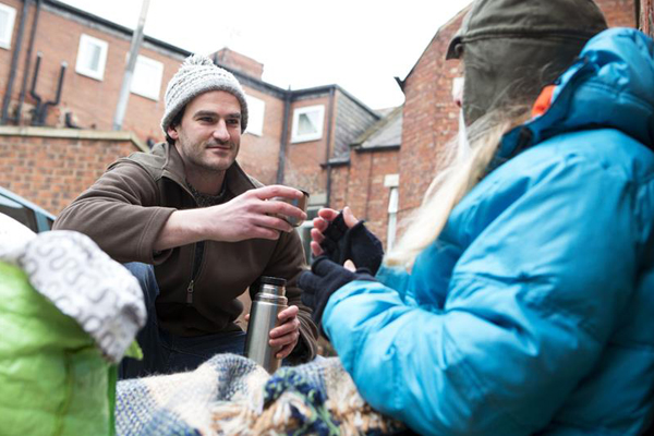 man-offering-hot-drink-from-flask-to-homeless-man_web_1600x1067_color